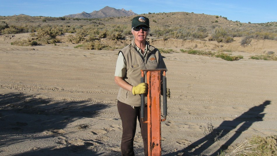 Volunteer installing a trail sign post on a wide road. Creosote in background.