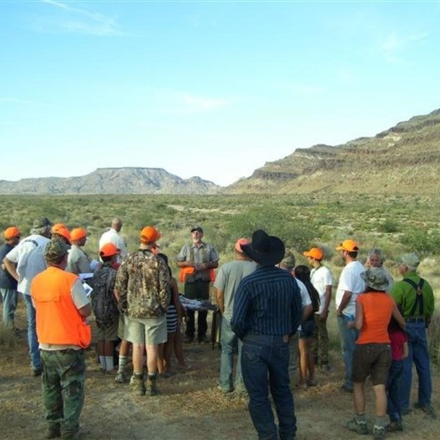 A group of parents and children in orange hats and vests gather for the Youth Quail Hunt with ranger