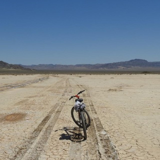 A bike in between tire tracks on Soda Dry Lake.  Mountains in the distance.