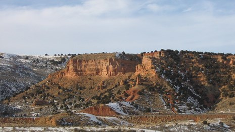 Towering sandstone cliffs, dusted with snow, line a canyon.