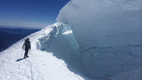 A climber stands on the edge of a large glacier crevasse.