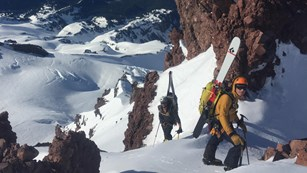 Two climbers scale a deep snowy slope high above the surrounding mountain ranges.