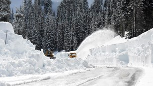 Two rotary plows clearing snow from a road.