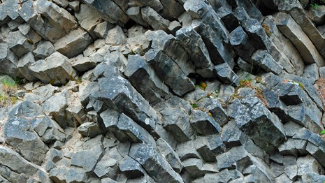 A cliff of roughly octagonal columns of grey rock.