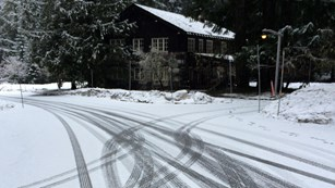 Tire tracks cross on a snowy road in front of a wood and stone building.