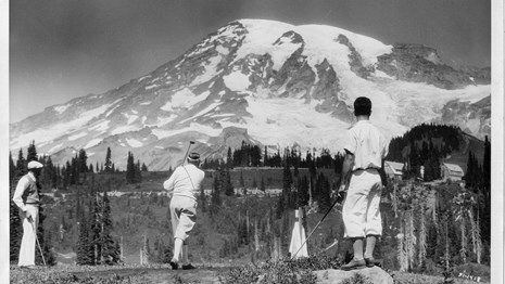 Men playing golf in subalpine meadows with Mount Rainier looming in the background