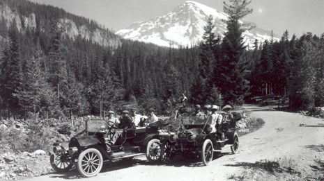 Two old cars on a forested road with Mount Rainier in the background