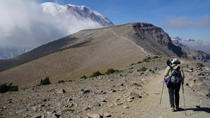 A hiker follows a trail along a ridge towards Mount Rainier.