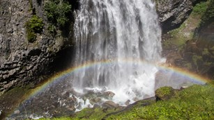 A rainbow arches through the spray of a waterfall cascading down a rocky cliff.