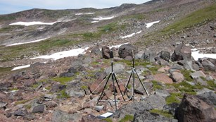 Two tripods with microphones set up on a rocky subalpine slope.