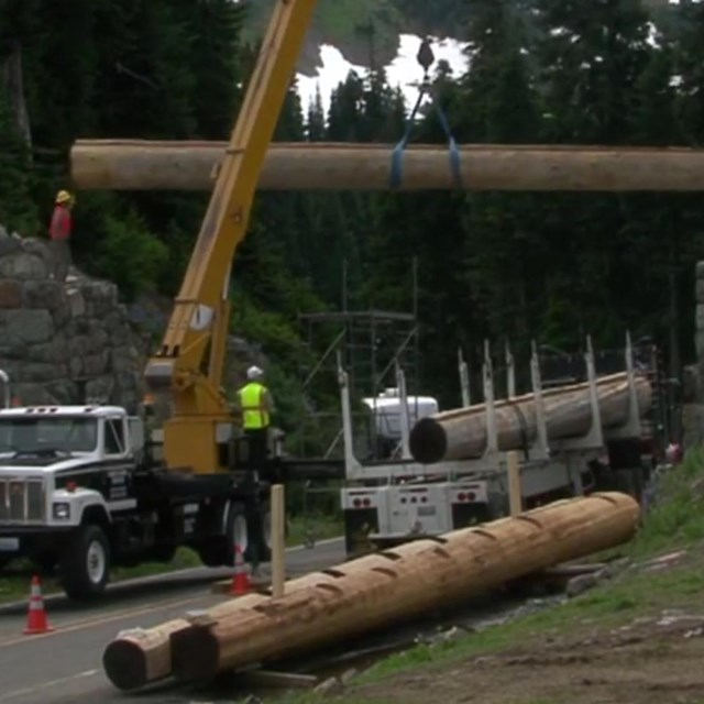 A large truck lifts a large log to span above a road between to rock walls.