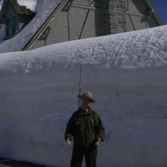 A ranger stands in front of a tall snowbank.