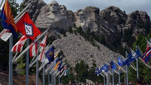 Visitors walking along the Avenue of Flags with Mount Rushmore in the background.