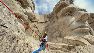 A Mount Rushmore ropes team member working near the chins of Abraham Lincoln and Theodore Roosevelt.