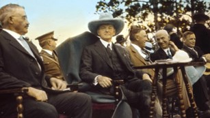 President Calvin Coolidge (center) sits next to Senator Peter Norbeck (left) at the 1927 dedication.