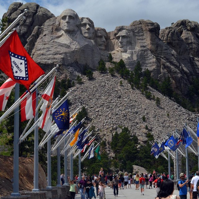Photo of visitors walking through the Avenue of Flags with Mount Rushmore in the background.