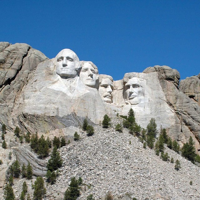 Photograph of Mount Rushmore under a clear blue sky.