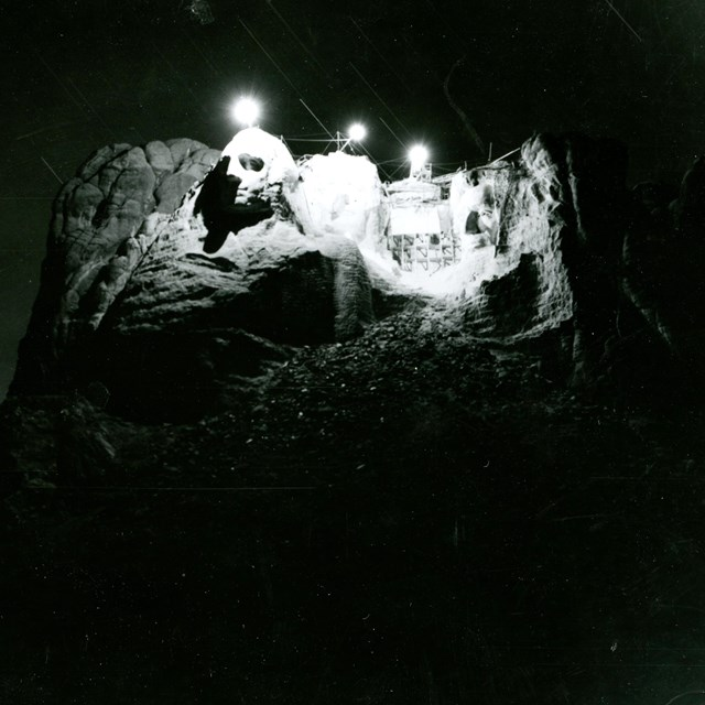Photo of an attempt in 1939 to illuminate Mount Rushmore from the top of the sculpture.