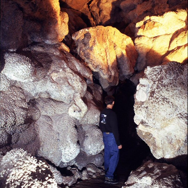 A visitor walking through Jewel Cave, surrounded by nailhead spar calcite crystals.