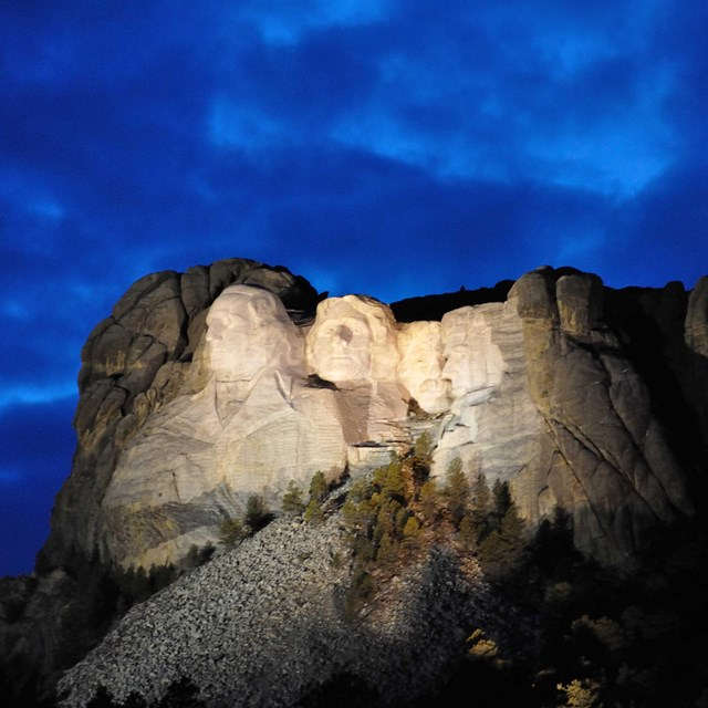 Mount Rushmore illuminated at dusk under a cloudy sky.