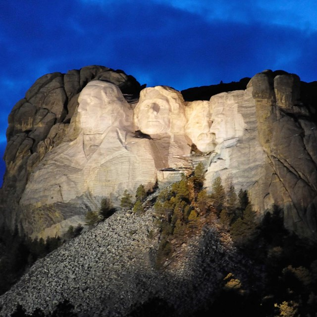 Mount Rushmore illuminated at night.