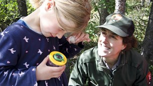 a girl looks into a magnifying box as a ranger looks on