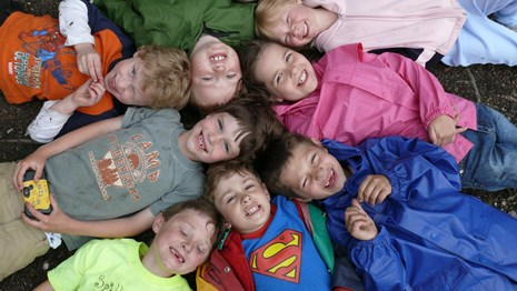 children lay on the ground in a circle smiling