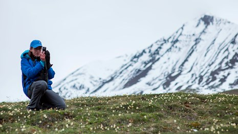 a woman kneels in front of a snowy mountain to take a picture