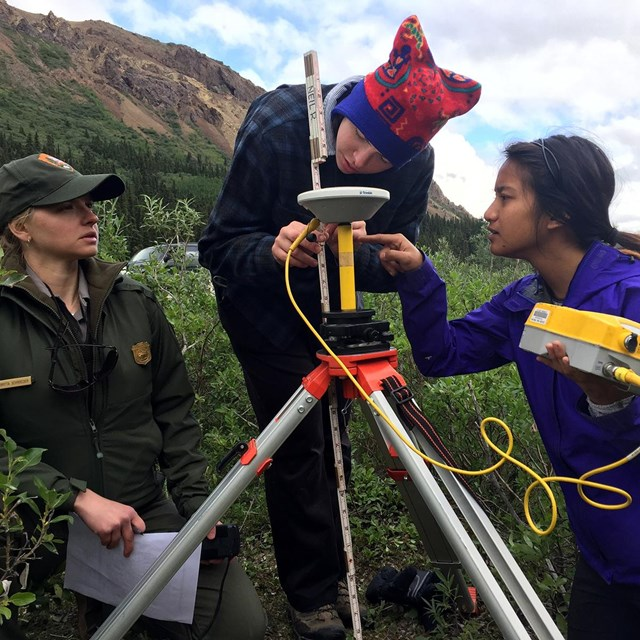students and a ranger use research equipment