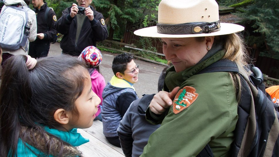 A child looks at a park ranger's National Park Service patch