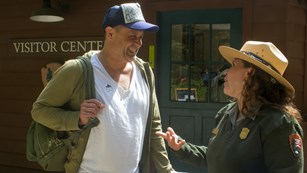 Ranger and Visitor have a conversation outside the Muir Woods visitor center