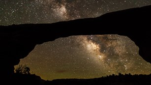 a massive stone arch with the Milky Way and stars overhead