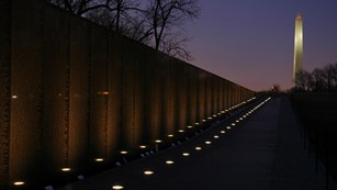 Vietnam Veterans Memorial at night, with Washington Monument in the background