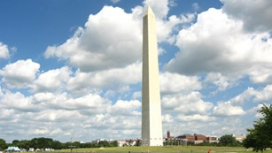 Washington Monument with blue sky and puffy clouds