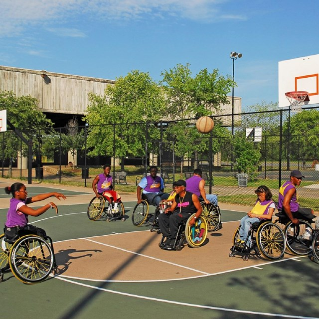 Group in wheelchairs playing basketball on an outdoor court