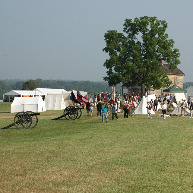 Crowd at a Civil War reeanctment camp with tents and cannons