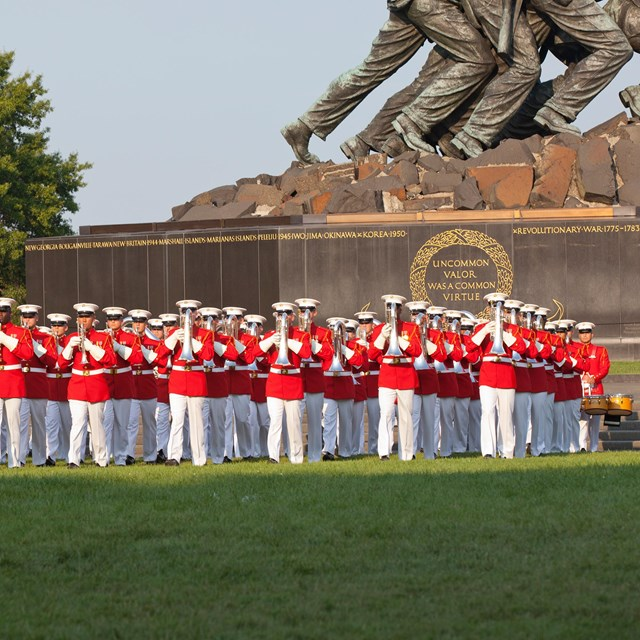US Marine Drum and Bugle Corps in formation at the base of a statue