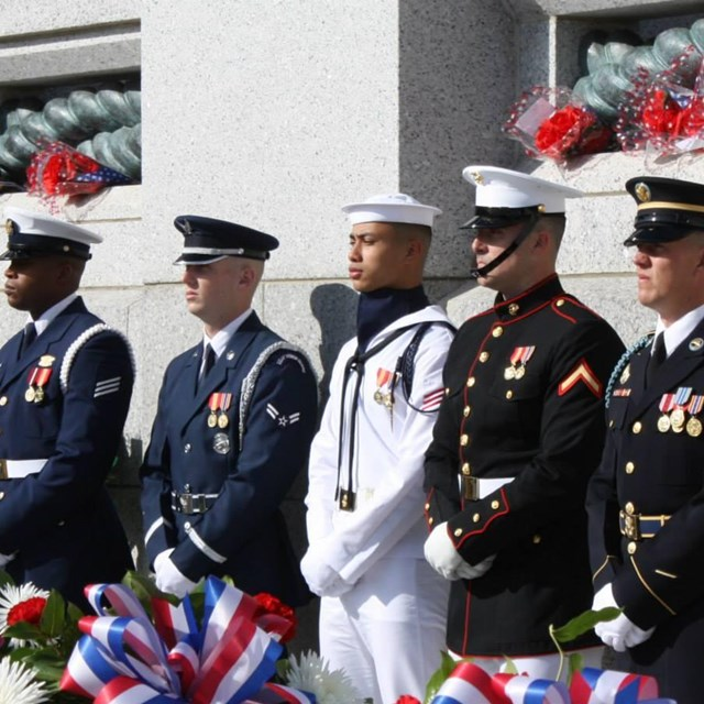 US military service members standing in front of a memorial wall