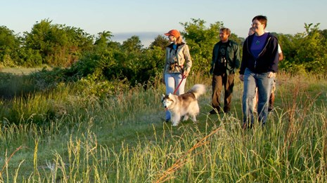 a family and their dog hike along a section of the trail in a prairie.