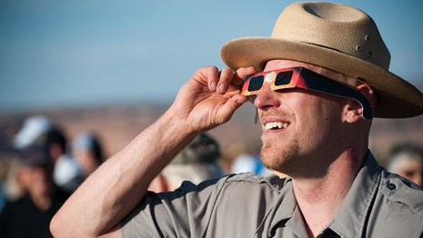 A ranger looks up at the sky through eclipse viewing glasses