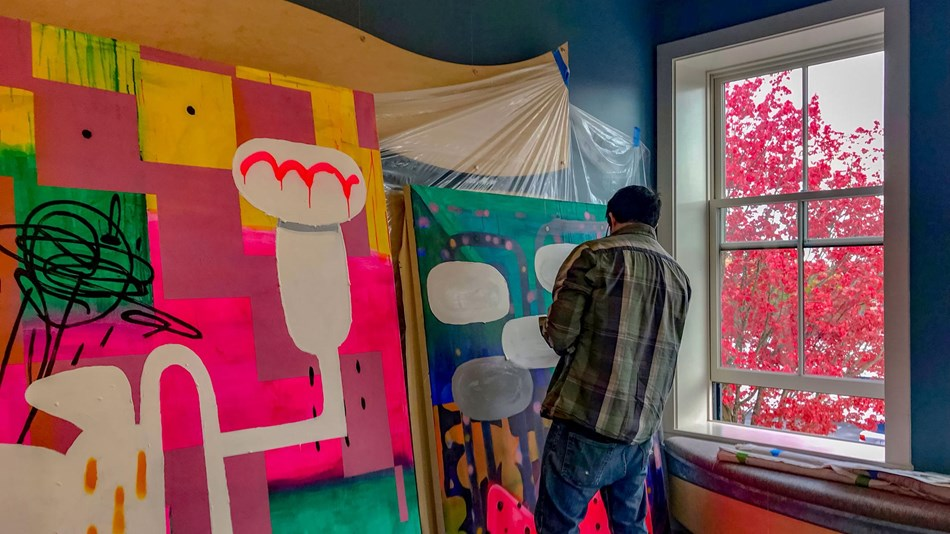 Nick Mello painting a large vibrant mural