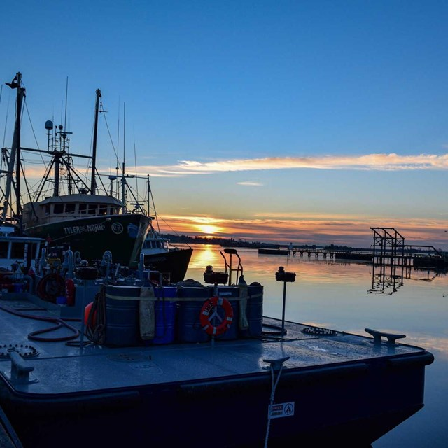 Sunset view of New Bedford Harbor with fishing boats at dock.