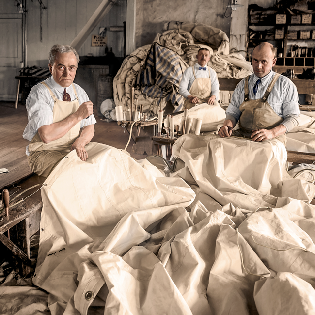 Colorized image of men working in a sail loft