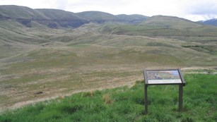 Vista of rolling hills and canyons with an information panel about the battle in the foreground.