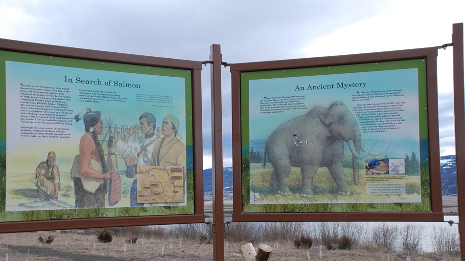 A sign with two informational panels about the history of Tolo Lake is situated on the Lake's Shore.