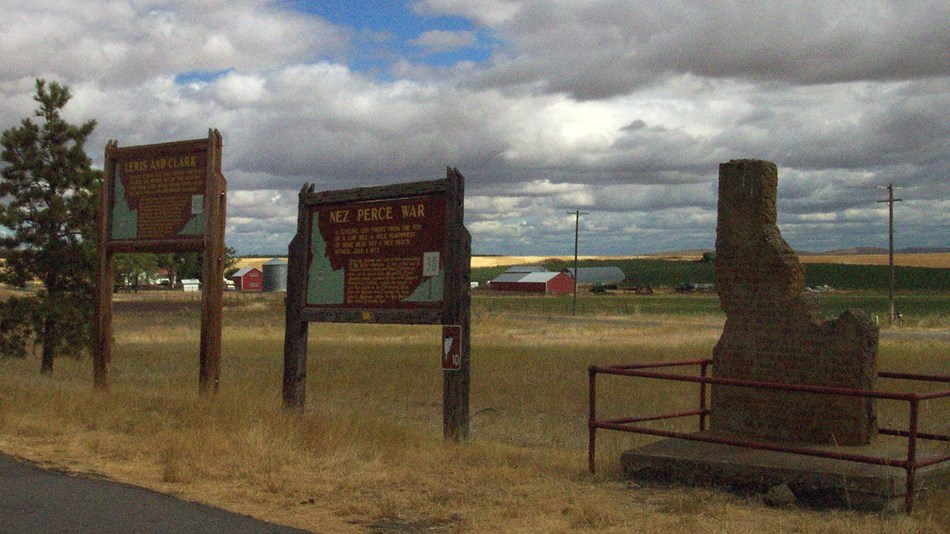 Two brown signs and a monument in the shape of Idaho on the side of the road.