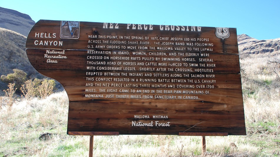 A wooden sign about the Nez Perce Crossing at Dug Bar with canyon walls in the background.