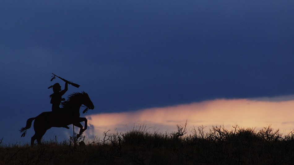 A metal silhouette of a Nez Perce on horseback with the sunset in the background.