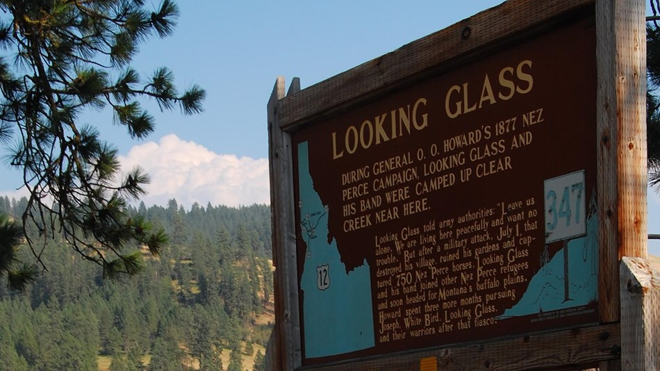 Wooden Information Sign about Looking Glass' Camp is situated near a scenic river.