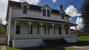 A white two story building with an outer porch.